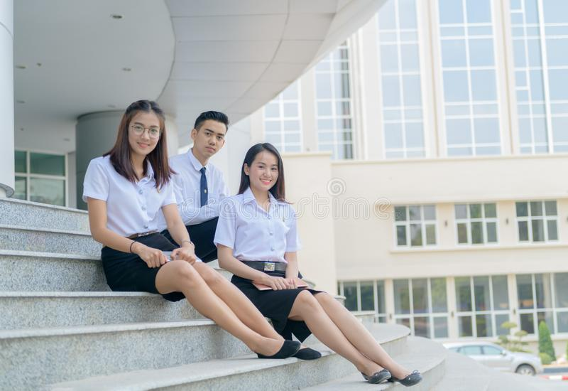 Happy asian students in uniform siting at university stock images