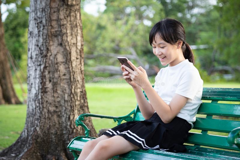 Happy asian teenage girl holding cellphone having fun,female people playing game,chat,talk to friends on the smartphone while royalty free stock photo