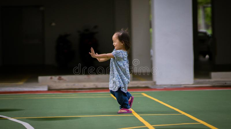 Happy Asian toddler kid is playing in the outdoors at the park. Happy Asian toddler kid is playing in the outdoors at the basketball court royalty free stock photo
