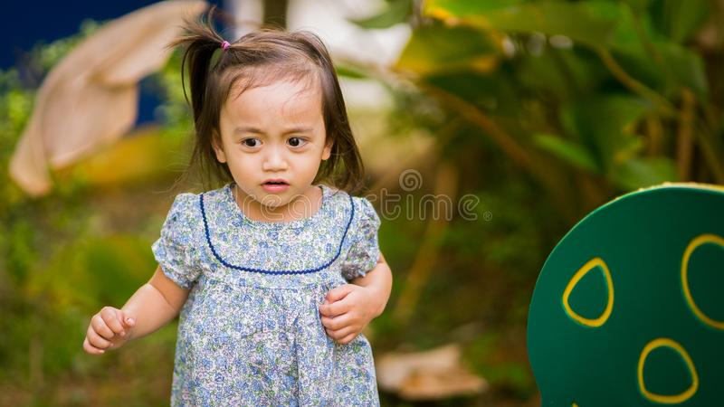 Happy Asian toddler kid is playing in the outdoors at the park. In Malaysia royalty free stock images