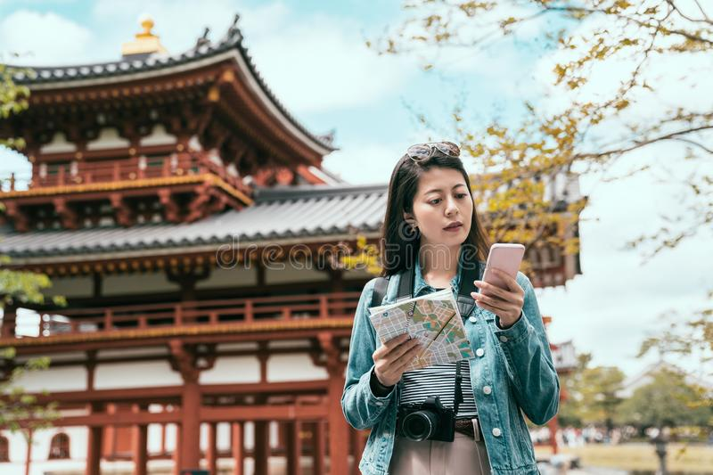 Happy asian tourist searching information on line. Portrait of happy asian tourist searching information on line in smart phone and paper map guidebook on royalty free stock images