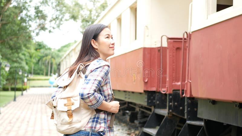 Happy Asian tourist woman with backpack walk to the train at railway station, begin travel alone. travel in Asia by vintage train. Leisure tourist travelling royalty free stock photography
