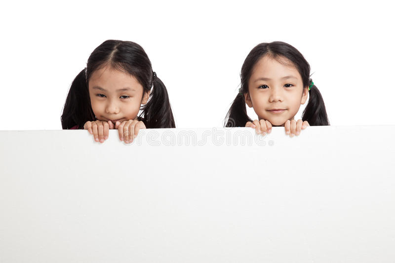 Happy Asian twins girls behind white blank banner. On white background stock photo