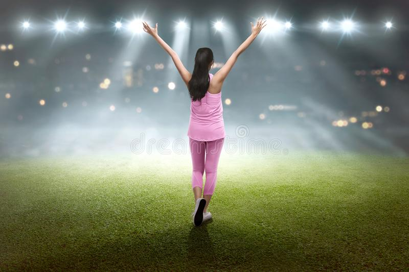 Happy asian woaman celebrating her victory. On the stadium stock images
