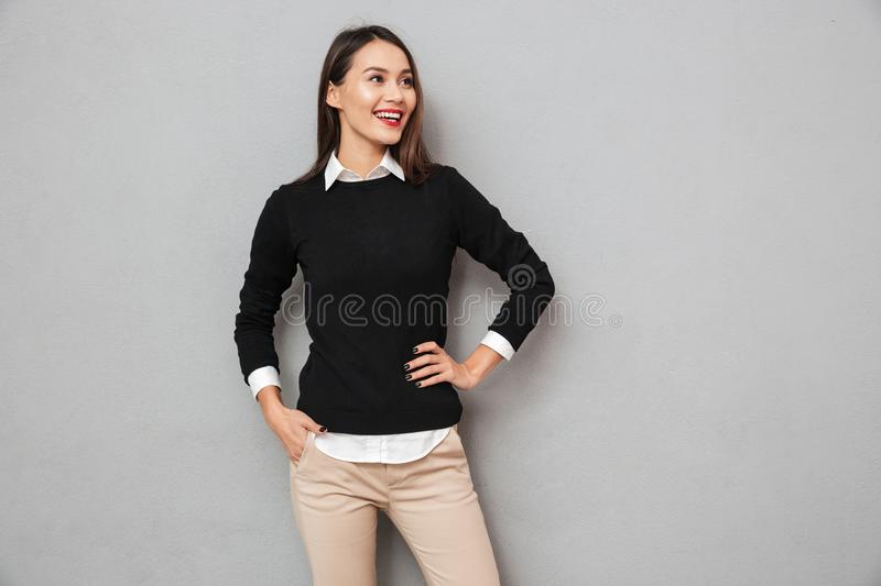 Happy asian woman in business clothes with arm on hip royalty free stock photo