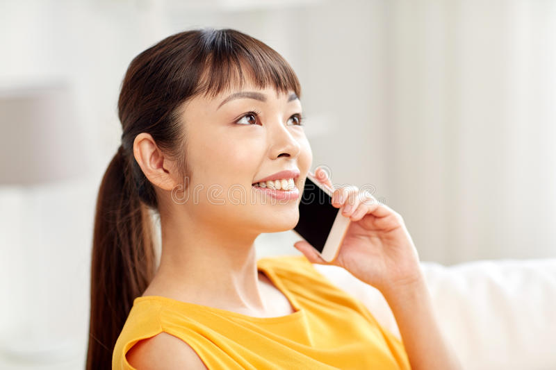 Happy asian woman calling on smartphone at home royalty free stock images