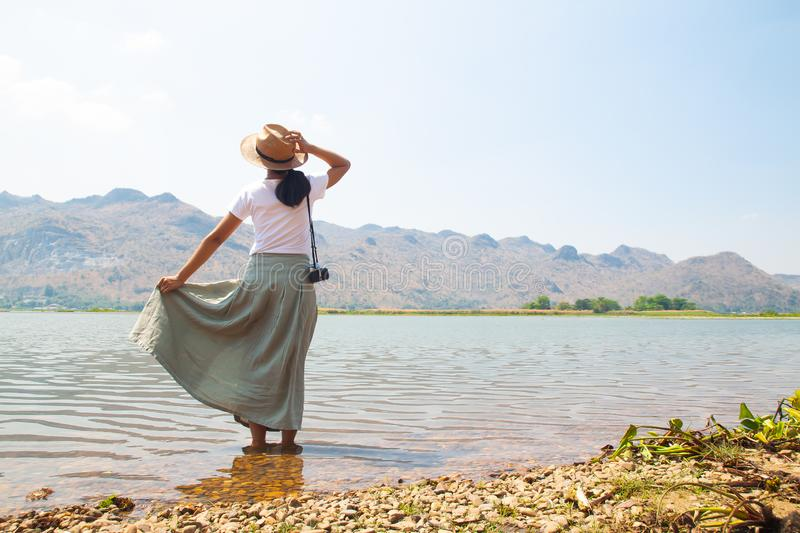 Happy asian woman in casual style clothing standing in the river with mountain view. On background royalty free stock photos