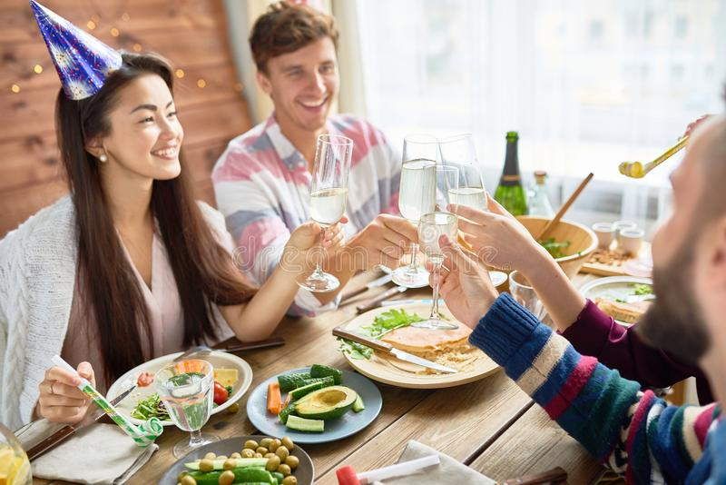 Happy Asian Woman Celebrating Birthday with Friends. Group of happy young people wearing holiday caps celebrating Birthday together clinking champagne glasses stock photo