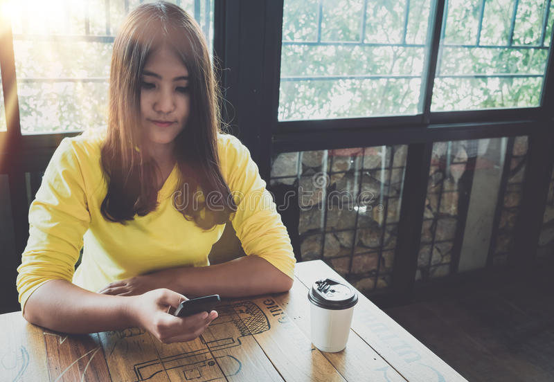 Happy Asian woman chatting on her mobile phone while relaxing in cafe during free time,. Charming and beautiful hipster girl with smile reading good news on stock image