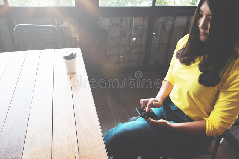 Happy Asian woman chatting on her mobile phone while relaxing in cafe during free time,. Charming and beautiful hipster girl with smile reading good news on royalty free stock photos