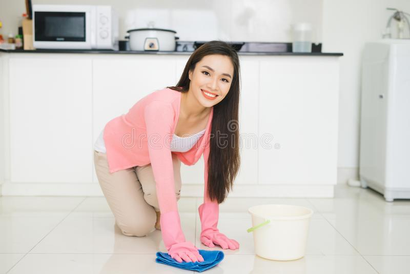 Happy asian woman cleans floor in the kitchen royalty free stock images