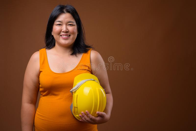 Happy Asian woman construction worker holding hardhat. Studio shot of beautiful overweight Asian woman construction worker holding hardhat against brown stock photos