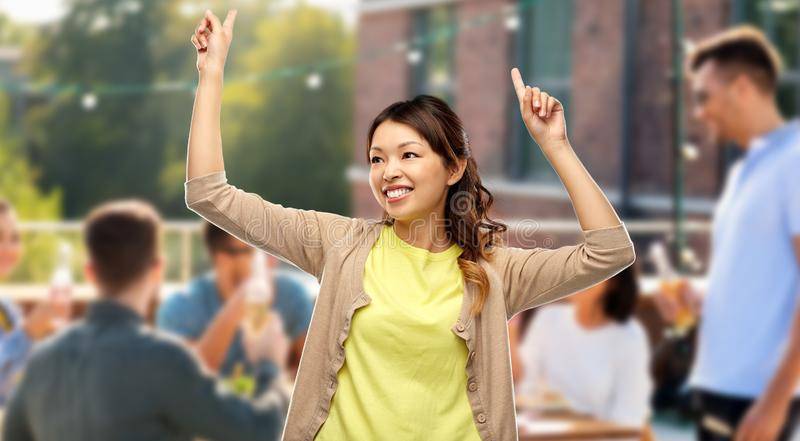 Happy asian woman dancing over rooftop party royalty free stock photo