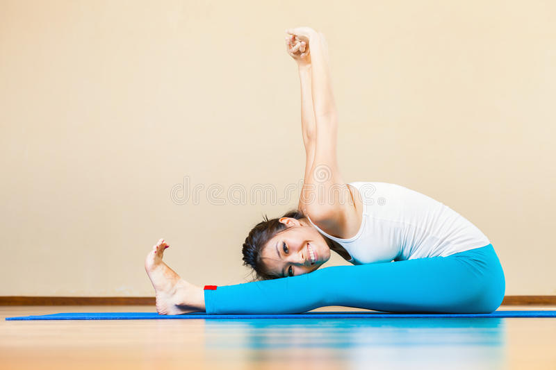 Happy asian woman doing exercise of yoga indoor at home. Happy and beautiful asian woman doing exercise of yoga indoor at home. She looking at camera and smiling royalty free stock photo