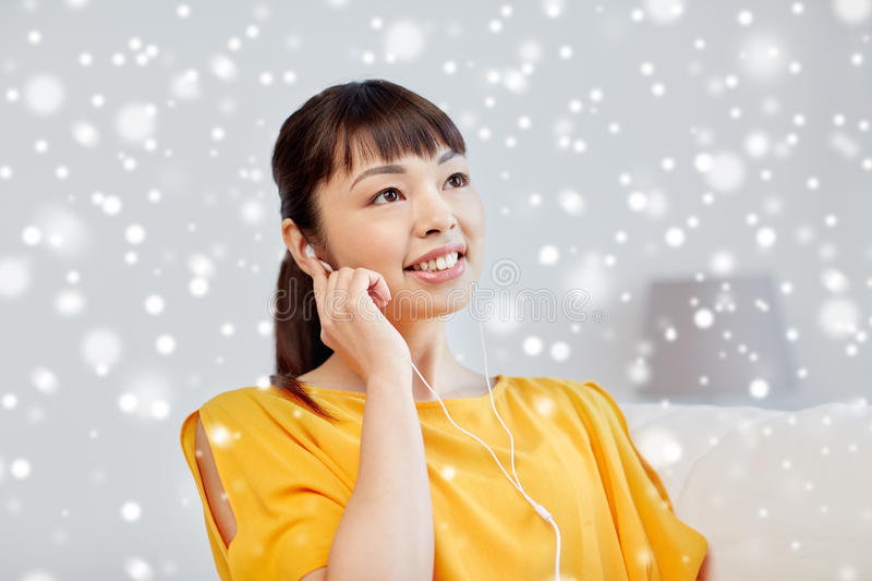 Happy asian woman with earphones listening music royalty free stock images