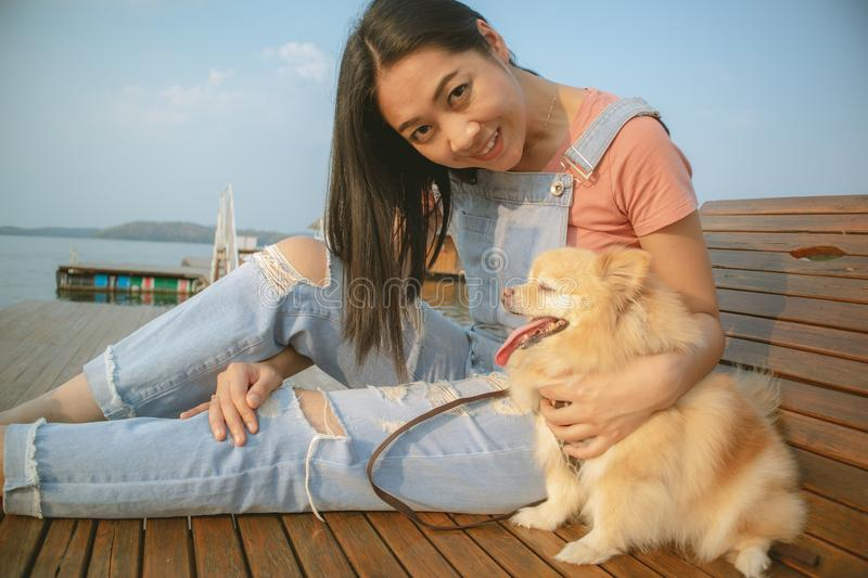 Happy Asian woman enjoy relax with her dog stock image