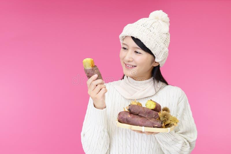 Woman holding baked sweet potatoes stock image