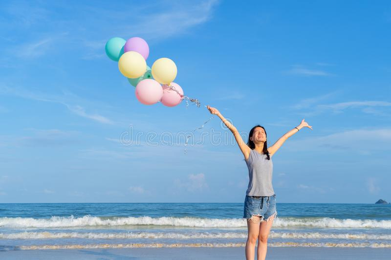 Happy Asian woman holding colorful balloons at the beach during travel trip on holidays vacation outdoors at ocean or nature sea. At noon, Phuket, Thailand royalty free stock image