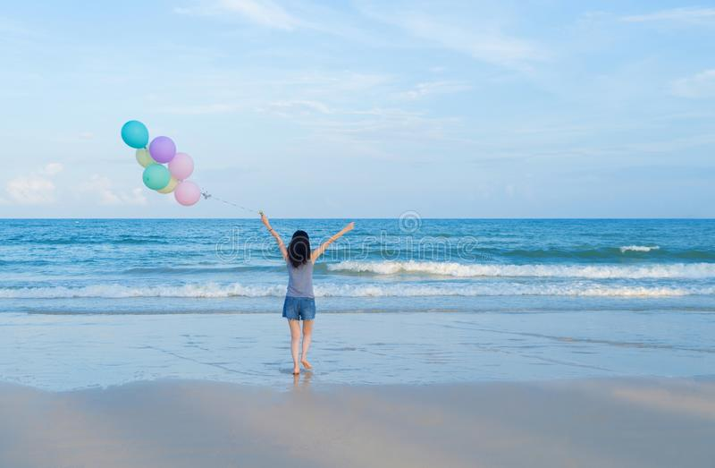 Happy Asian woman holding colorful balloons at the beach during travel trip on holidays vacation outdoors at ocean or nature sea. At noon, Phuket, Thailand royalty free stock photo
