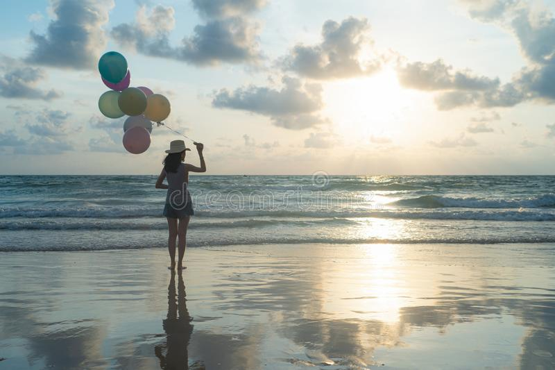 Happy Asian woman holding colorful balloons at the beach during travel trip on holidays vacation outdoors at ocean or nature sea. At noon, Phuket, Thailand stock photos