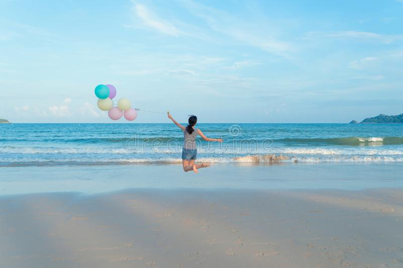 Happy Asian woman holding colorful balloons at the beach during travel trip on holidays vacation outdoors at ocean or nature sea. At noon, Phuket, Thailand stock photography