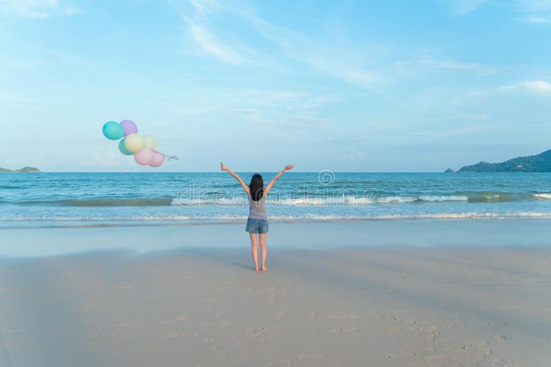 Happy Asian woman holding colorful balloons at the beach during travel trip on holidays vacation outdoors at ocean or nature sea. At noon, Phuket, Thailand stock images