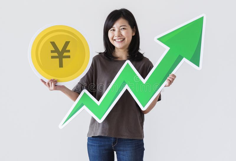 Happy Asian woman holding a Japanese Yen icon stock photography