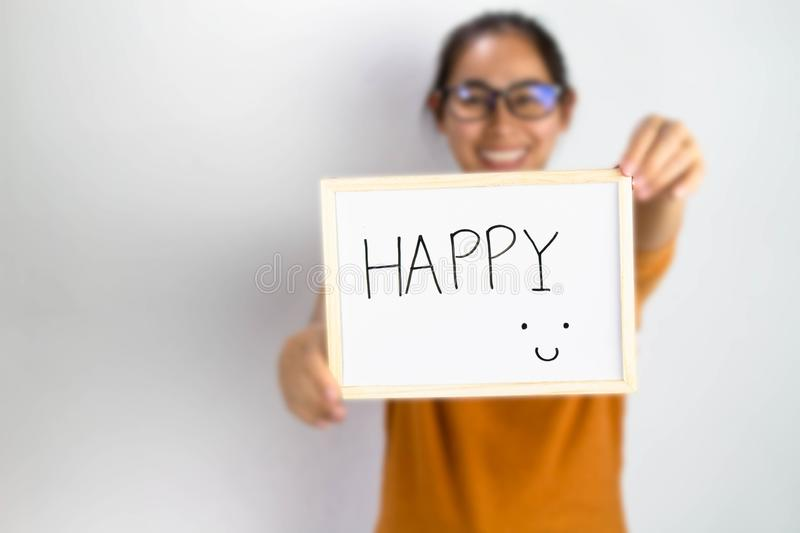 Happy Asian woman holding a Happy sign writing on whiteboard with handwriting.  on white background royalty free stock photo