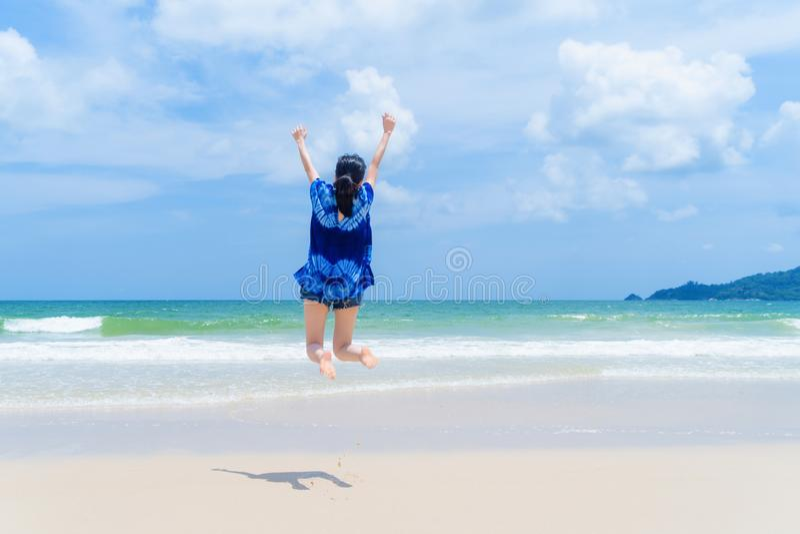 Happy Asian woman jumping, relaxing and enjoying at the beach during travel holidays vacation outdoors at ocean or nature sea at stock photos