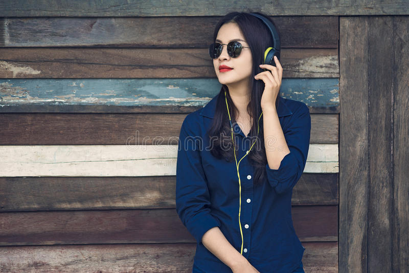 happy asian woman listening to music on her headphone and holding smartphone, leaning aginst old wooden barn wall, vintage retro stock photos