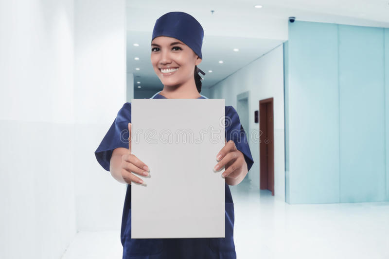 Happy asian woman nurse showing empty white board royalty free stock photo