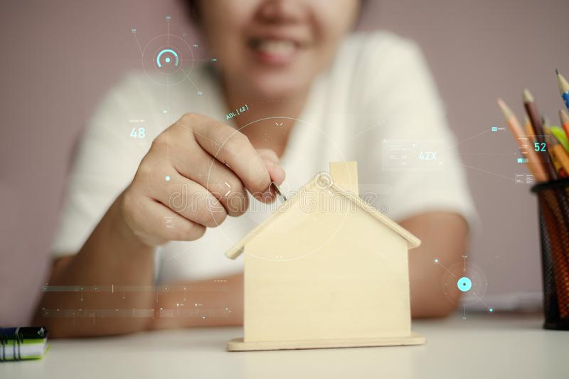 Happy Asian woman putting money coin to the wooden house piggy bank metaphor saving money for buy the house with HUD user stock photo