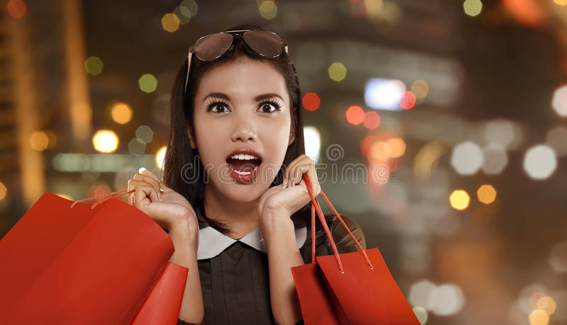 Happy asian woman with red shopping bag celebrating Black Friday. On the mall stock photography