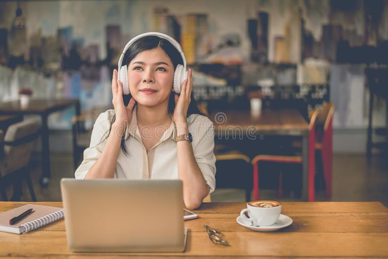 Happy Asian woman relaxing and listening music in coffee shop wi royalty free stock photo