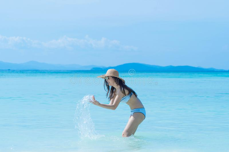 Happy Asian woman, a sexy Thai lady, relaxing and enjoying at turquoise sea near Phuket beach in summer during travel holidays royalty free stock images