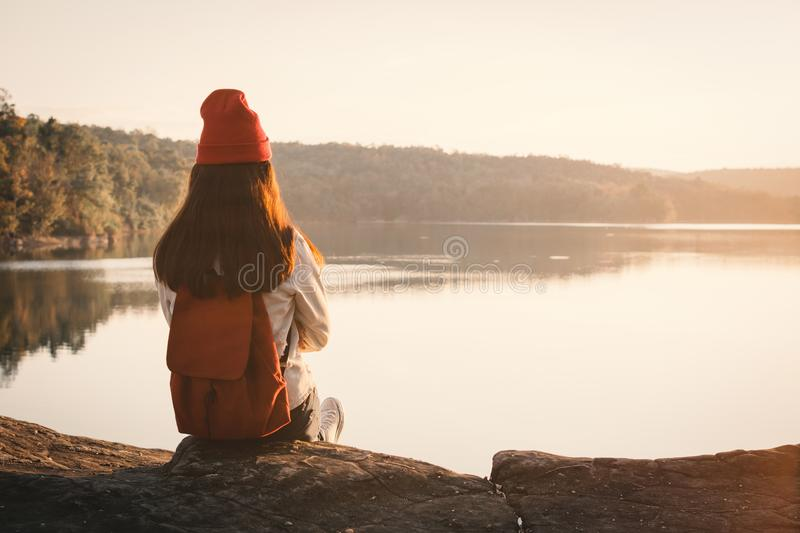 Happy Asian woman sitting on rock in nature during sunset royalty free stock image