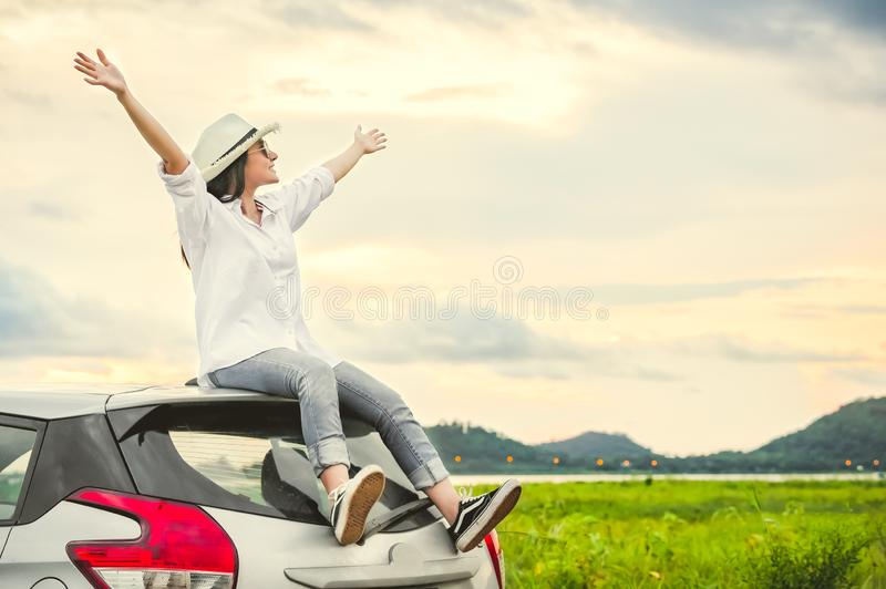 Happy Asian woman spread arms widely and breathed fresh air with happiness mood in evening after sunset on car roof. People. Lifestyle in long vacation trip stock photos