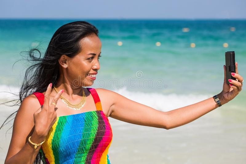 Happy asian woman is taking a selfie at the beach. Beautiful young asian woman is taking a selfie with her phone while standing at the beach. Victory gesture stock image