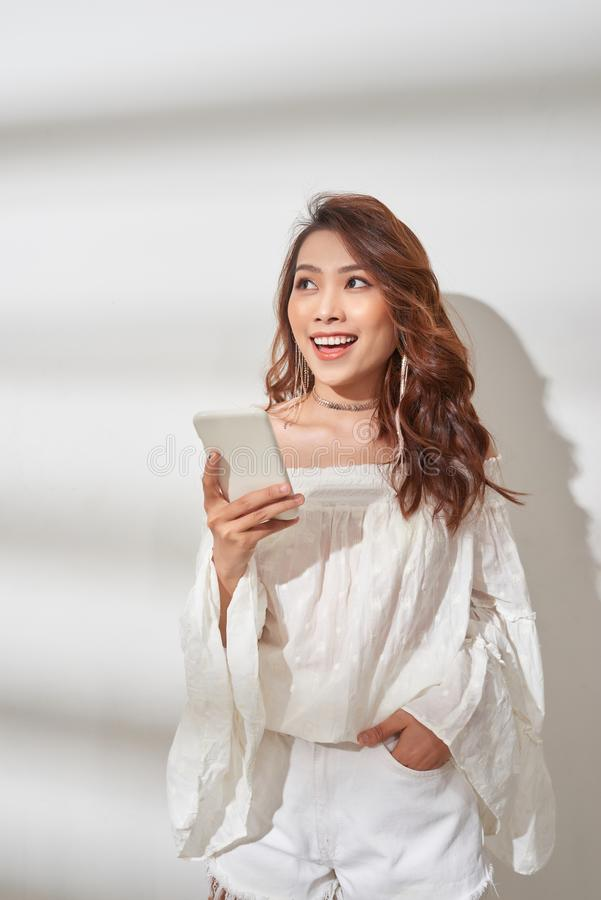 Happy asian woman in trendy clothes holding smartphone and rejoices while looking at the camera over white background.  royalty free stock image