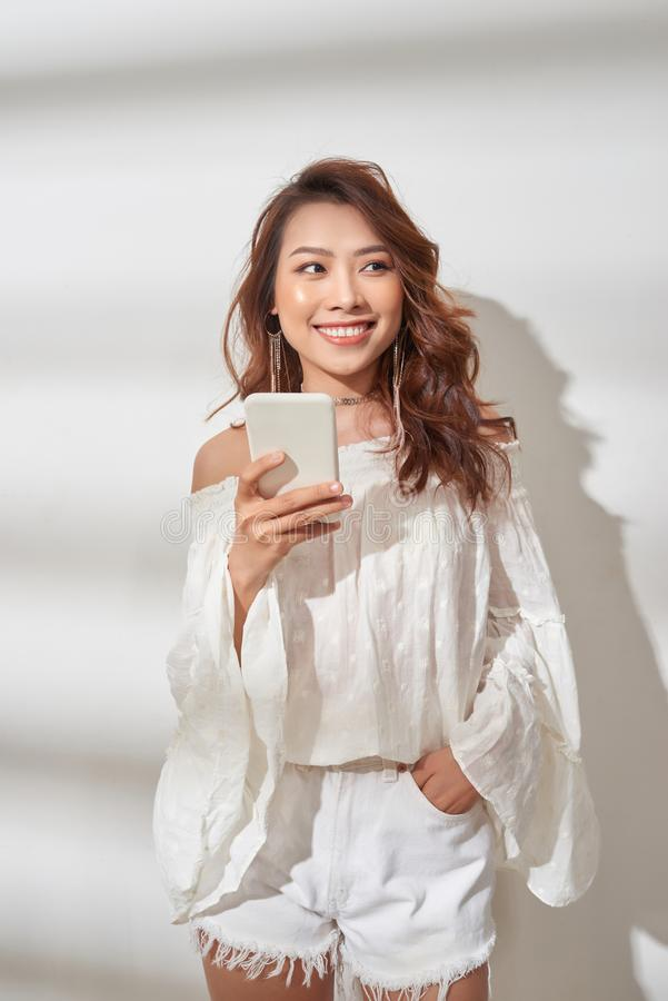 Happy asian woman in trendy clothes holding smartphone and rejoices while looking at the camera over white background.  stock photo