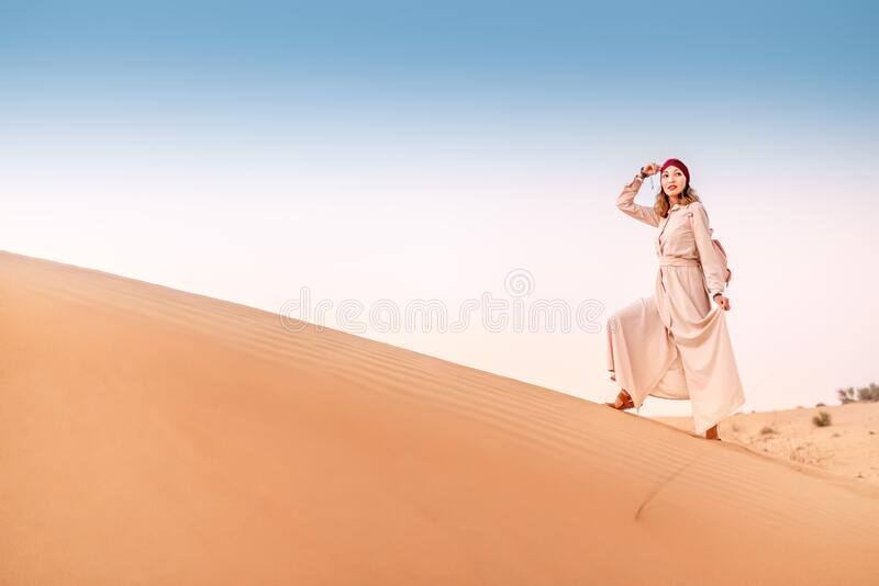 Asian woman in turban travels in Sahara desert. Adventure and life experience concept. Happy asian woman in turban travels in Sahara desert. Adventure and life stock photo