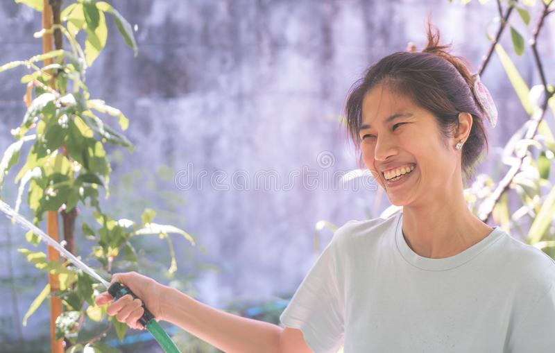 Happy Asian woman watering garden at home stock photo