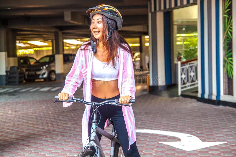 Happy woman wearing helmet riding bicycle in the summer. stock photos