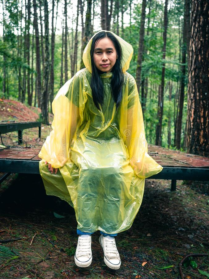 Happy Asian woman wearing yellow raincoat sitting on wooden stage in rain royalty free stock image