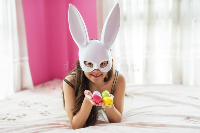 girl with bunny mask hold easter eggs stock image