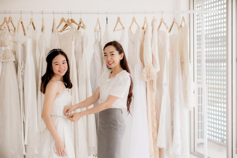 Happy asian women designer making adjustment in fashion studio,Asian bride smling and trying on wedding dress royalty free stock photography