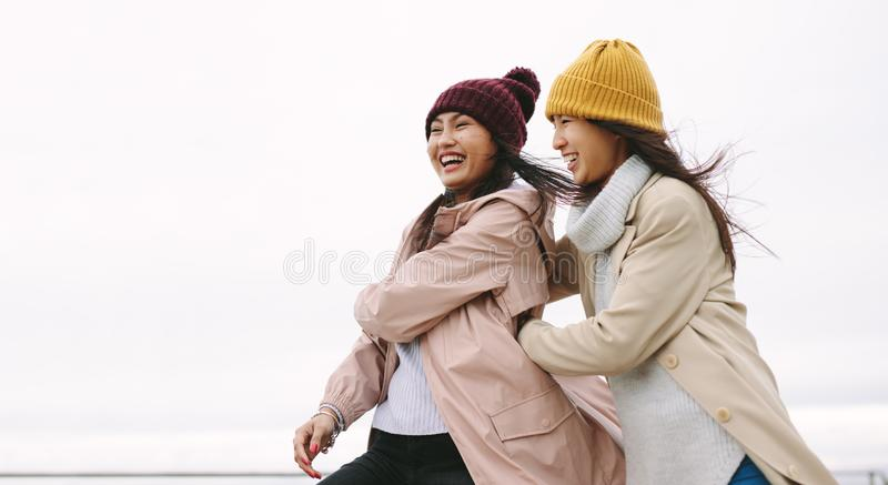 Two asian women in winter clothes standing together outdoors stock images