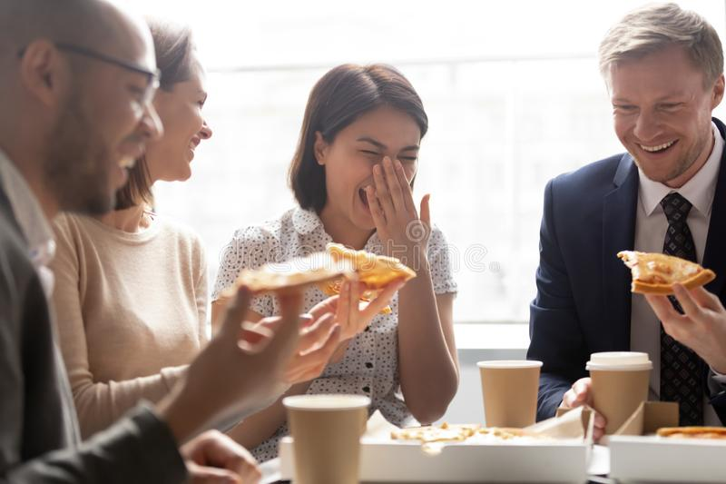 Happy asian worker laugh hold slice eating pizza with colleagues royalty free stock photography