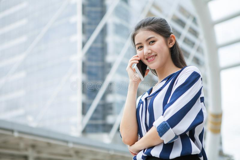Happy asian young business woman talking on mobile phone in urban city . outdoor stock photos