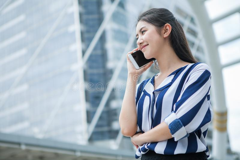 Happy asian young business woman talking on mobile phone in city . outdoor stock photography